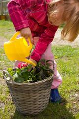 Mädchen mit Gießkanne beim Blumen gießen
