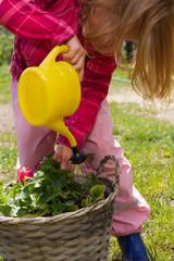 blondes Mädchen beim Blumen gießen