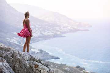 Young woman standing on rock and enjoying beautiful view