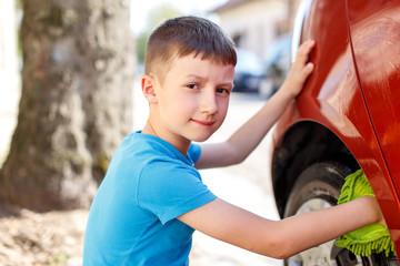 Little kid cleaning car wheel