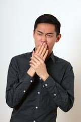 Disgusted young Asian man covering his mouth with hands
