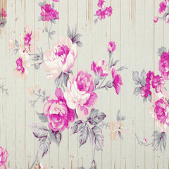 Rose vintage from fabric on wooden background.