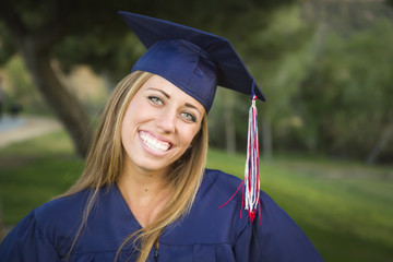 Young Woman Wearing Cap and Gown Outdoors