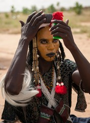Wodaabe man checking makeup in a mirror, Gerewol, Niger