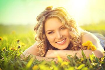 Beautiful young woman lying on a field, enjoying nature