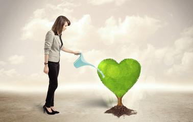 Business woman watering heart shaped green tree