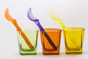 cucchiai colorati dentro bicchieri colorati