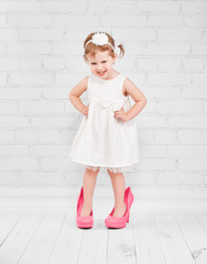little girl fashionista in  big pink heeled shoes