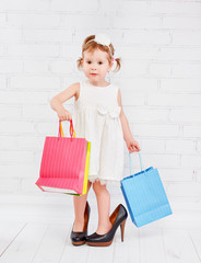 funny little girl fashionista in big lady heeled shoes went on s