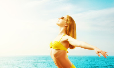 young happy woman on the beach in a bikini