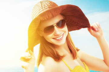 young happy woman on the beach in  sunglasses and a hat
