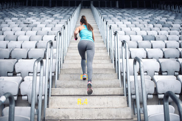 Portrait of healthy girl working out and running on stairs