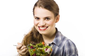 Beautiful, young woman eating vegetable salad
