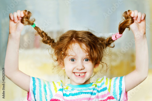 Poster Laughing girl pull her pigtail up by hand and show her teeths.