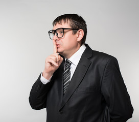 Young businessman in glasses shows quietly