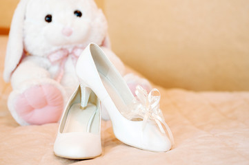 wedding bridal shoes and plush toy bunny. White shoe of the