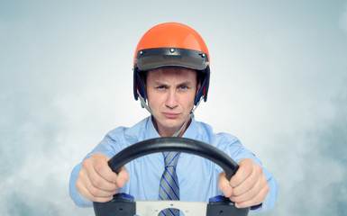 Businessman in a helmet with steering wheel, car drive concept