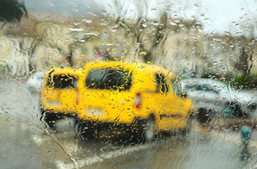 View through the car windscreen of the parking under rain.