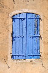 Closed shuttered window of French village house.