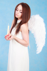 Beautiful young angel with a candle