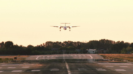 Commercial plane landing at dusk