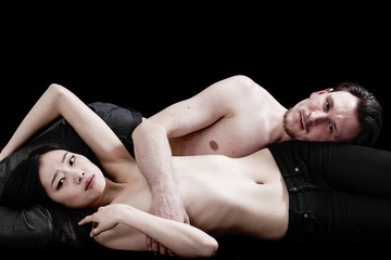 Beautiful and intimate bare-chested couple portrait lying togeth