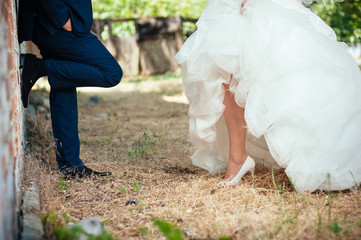 Happy young bride and groom outdoors in the park on their
