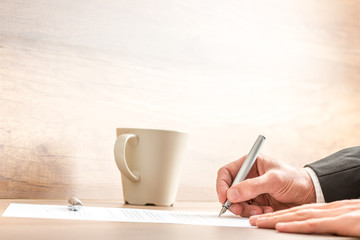 Businessman writing with a pen on a paper sheet