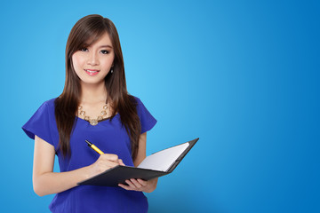 Young Asian woman holding pen and notebook, on blue background
