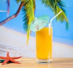 glass of orange juice on the sandy beach near starfish
