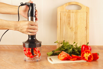 Hands chefs are going to shred red pepper in a blender