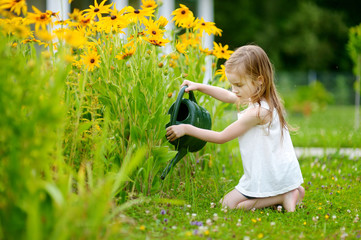 Cute girl watering plants in the garden