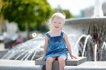 Cute toddler girl playing with a city fountain
