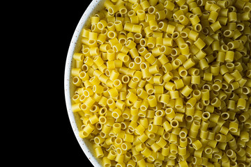 Ditalini pasta in a bowl on a black background