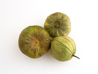 Whole tomatillos on a white cutting board