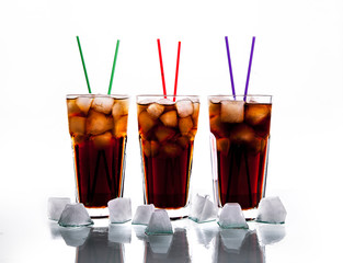 three glasses of cola with ice and straws on a white background.