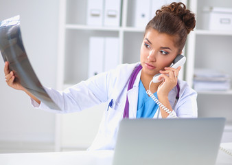 Female doctor looking x-ray scan and talking on phone in