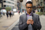 Young African Asian man in New York City texting cell phone - 82659162