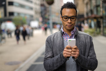 Young African Asian man in New York City texting cell phone