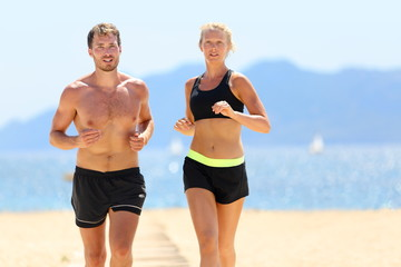 Fitness running couple exercising cardio on beach