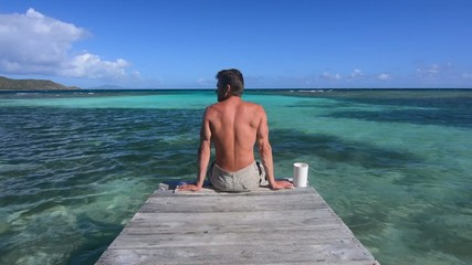 Man sits on wooden dock over shallow Caribbean waters