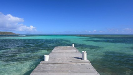 Wooden dock extending into tropical turquoise sea