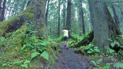 Man jogs on trail through beautiful northwest forest