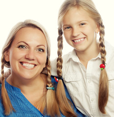 Portrait of a joyful mother and her daughter smiling at the came