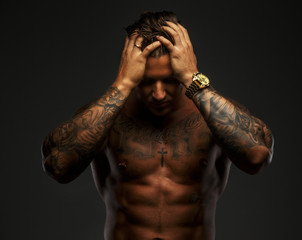 Muscular man with tattooes in deep shadows