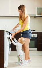 Mother and child using washing machine
