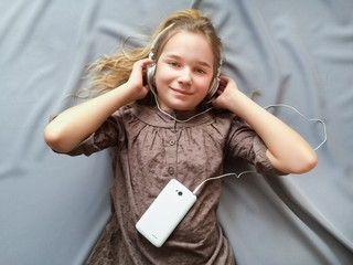 Young girl lying on the bed and listening to music