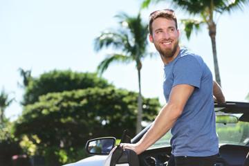 Happy man driver driving his new convertible car