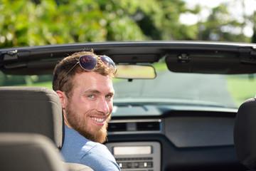 Car driver man driving convertible on a road trip