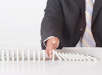 Hand stopping domino effect. Concept image for problem solving
